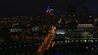 DX0001_002799 - 5.7K stock footage aerial video of passing by the city skyline, and bridge spanning the river at night, Downtown Columbus, Ohio