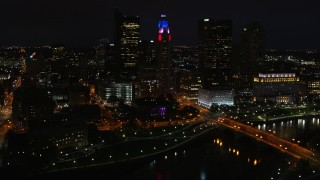 DX0001_002801 - 5.7K stock footage aerial video of flying by LeVeque Tower and bridge spanning the river at night, Downtown Columbus, Ohio