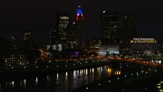 DX0001_002804 - 5.7K stock footage aerial video of LeVeque Tower and bridge spanning the river at night seen during descent, Downtown Columbus, Ohio