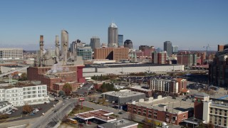 DX0001_002805 - 5.7K stock footage aerial video of the city skyline seen while flying by brick factory, Downtown Indianapolis, Indiana