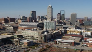 DX0001_002845 - 5.7K stock footage aerial video fly away from arena and by the city's skyline in Downtown Indianapolis, Indiana