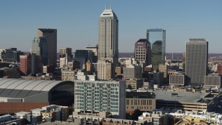 DX0001_002860 - 5.7K stock footage aerial video of slowly flying by tall skyscrapers in the city's skyline, reveal arena in Downtown Indianapolis, Indiana