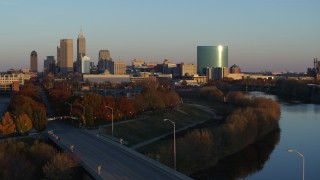 DX0001_002926 - 5.7K stock footage aerial video of the city's skyline at sunset seen from White River, reveal bridge, Downtown Indianapolis, Indiana