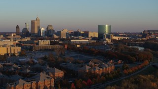 DX0001_002927 - 5.7K stock footage aerial video of the city's skyline at sunset seen while ascending from White River, Downtown Indianapolis, Indiana