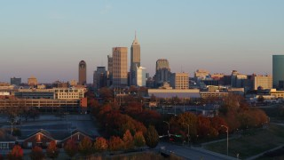 DX0001_002931 - 5.7K stock footage aerial video of the city's skyline at sunset, seen during ascent from trees, Downtown Indianapolis, Indiana