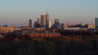 DX0001_002936 - 5.7K stock footage aerial video descend behind trees with wide view of the city's downtown skyline at sunset, Downtown Indianapolis, Indiana