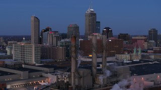 DX0001_002960 - 5.7K stock footage aerial video flyby smoke stacks for view of city skyline at twilight in Downtown Indianapolis, Indiana