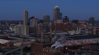 DX0001_002962 - 5.7K stock footage aerial video fly past smoke stacks at twilight with skyline in background, Downtown Indianapolis, Indiana