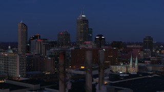 DX0001_002970 - 5.7K stock footage aerial video flyby giant skyscrapers of the city skyline at twilight, reveal smoke stacks, Downtown Indianapolis, Indiana