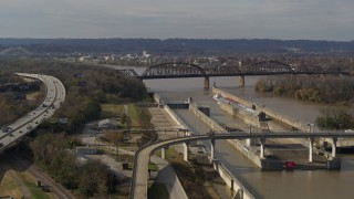 DX0001_003016 - 5.7K stock footage aerial video flying by railroad bridge near locks and a dam on the Ohio River in Louisville, Kentucky