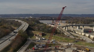 DX0001_003017 - 5.7K stock footage aerial video construction crane near railroad bridge and locks and a dam on the Ohio River in Louisville, Kentucky
