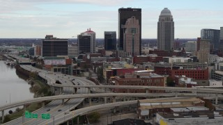 DX0001_003023 - 5.7K stock footage aerial video descend near freeway with view of skyscrapers in Downtown Louisville, Kentucky