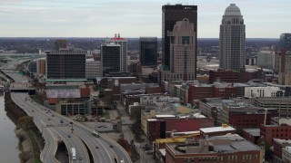 DX0001_003025 - 5.7K stock footage aerial video fly away from skyscrapers in Downtown Louisville, Kentucky, descend by freeway