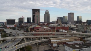 DX0001_003026 - 5.7K stock footage aerial video ascend over freeway to approach the city skyline in Downtown Louisville, Kentucky
