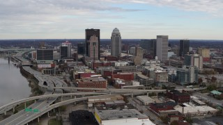 DX0001_003028 - 5.7K stock footage aerial video fly away from the city's skyline beside a freeway in Downtown Louisville, Kentucky