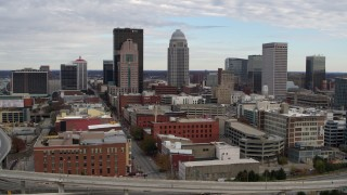 DX0001_003030 - 5.7K stock footage aerial video slow pass by the city's skyline beside a freeway in Downtown Louisville, Kentucky