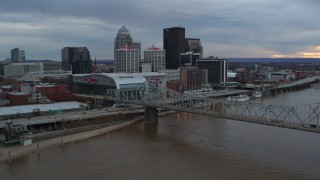 DX0001_003065 - 5.7K stock footage aerial video of arena and city skyline seen from bridge spanning river at sunset, Downtown Louisville, Kentucky