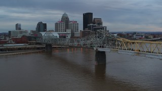 DX0001_003067 - 5.7K stock footage aerial video descend by bridge with view of the skyline at sunset, Downtown Louisville, Kentucky