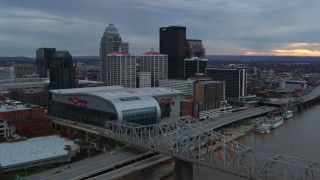 DX0001_003068 - 5.7K stock footage aerial video flyby bridge and ascend near arena and skyline at sunset, Downtown Louisville, Kentucky