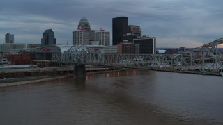 DX0001_003071 - 5.7K stock footage aerial video of flying by bridge and and ascend near the arena and city skyline at sunset, Downtown Louisville, Kentucky