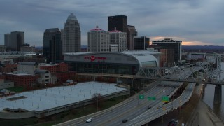 DX0001_003072 - 5.7K stock footage aerial video descend by freeway near the arena and city skyline at sunset, Downtown Louisville, Kentucky