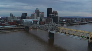 DX0001_003074 - 5.7K stock footage aerial video ascend by bridge spanning river at sunset for view of skyline, Downtown Louisville, Kentucky