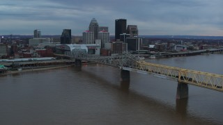 DX0001_003075 - 5.7K stock footage aerial video reverse view of bridge spanning river and city skyline at sunset, Downtown Louisville, Kentucky