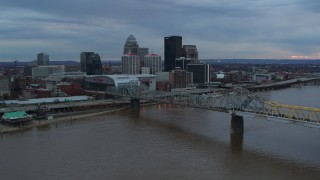 DX0001_003076 - 5.7K stock footage aerial video fly over the river to approach arena and city skyline at sunset, Downtown Louisville, Kentucky