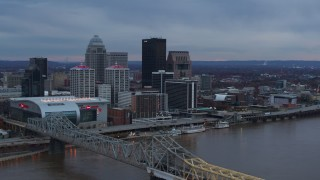 DX0001_003081 - 5.7K stock footage aerial video reverse view of city skyline at sunset while ascending by the bridge, Downtown Louisville, Kentucky