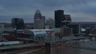DX0001_003089 - 5.7K stock footage aerial video flyby the arena, city skyline, and bridge over the river at sunset, Downtown Louisville, Kentucky