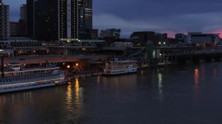 DX0001_003093 - 5.7K stock footage aerial video orbit small riverboat at twilight in Downtown Louisville, Kentucky