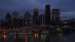 DX0001_003096 - 5.7K stock footage aerial video reverse view of the skyline at twilight, seen from Ohio River, Downtown Louisville, Kentucky