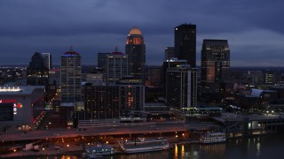 DX0001_003098 - 5.7K stock footage aerial video of flying by the skyline lit up at twilight, seen during ascent from Ohio River, Downtown Louisville, Kentucky