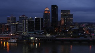 DX0001_003101 - 5.7K stock footage aerial video of reverse view of the skyline lit up at twilight, and the Ohio River, Downtown Louisville, Kentucky