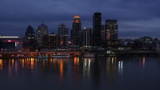 DX0001_003102 - 5.7K stock footage aerial video of the skyline lit up at twilight across the Ohio River, Downtown Louisville, Kentucky