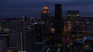 DX0001_003107 - 5.7K stock footage aerial video reverse view of a tall skyscraper and skyline lit up at twilight, Downtown Louisville, Kentucky