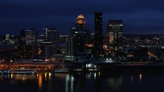 DX0001_003117 - 5.7K stock footage aerial video cross the Ohio River and ascend toward the city skyline at twilight, Downtown Louisville, Kentucky