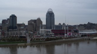 DX0001_003124 - 5.7K stock footage aerial video ascend over river for a view of the baseball stadium and skyscraper, Downtown Cincinnati, Ohio