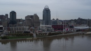 DX0001_003129 - 5.7K stock footage aerial video slow pass over river with view of the baseball stadium and skyscraper, Downtown Cincinnati, Ohio