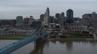DX0001_003130 - 5.7K stock footage aerial video slow pass over bridge and river with view of city skyline, Downtown Cincinnati, Ohio