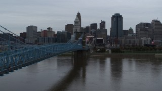 DX0001_003136 - 5.7K stock footage aerial video descend by bridge toward river, with view of the city skyline, Downtown Cincinnati, Ohio