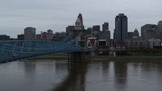 DX0001_003137 - 5.7K stock footage aerial video ascend by bridge from river toward the city skyline, Downtown Cincinnati, Ohio