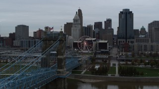DX0001_003138 - 5.7K stock footage aerial video descend by bridge to reveal river while focused on the city skyline, Downtown Cincinnati, Ohio