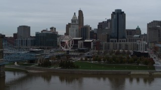 DX0001_003141 - 5.7K stock footage aerial video fly over Ohio River to approach Ferris wheel and skyline, Downtown Cincinnati, Ohio