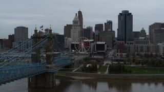 DX0001_003142 - 5.7K stock footage aerial video fly away from Ferris wheel and skyline, seen from bridge, and reveal river, Downtown Cincinnati, Ohio