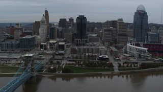 DX0001_003145 - 5.7K stock footage aerial video slow pass by city skyline, seen from the Ohio River near bridge, Downtown Cincinnati, Ohio