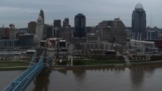 DX0001_003149 - 5.7K stock footage aerial video descend toward the river by bridge while focused on skyline, Downtown Cincinnati, Ohio