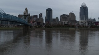 DX0001_003150 - 5.7K stock footage aerial video descend toward the river by bridge while focused on city skyline, Downtown Cincinnati, Ohio