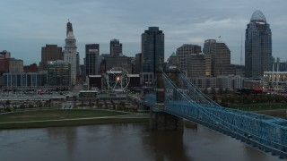 DX0001_003151 - 5.7K stock footage aerial video follow bridge over the river toward the city skyline at sunset, Downtown Cincinnati, Ohio