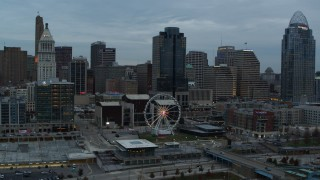 DX0001_003152 - 5.7K stock footage aerial video flyby the Ferris wheel and away from the city skyline at sunset, Downtown Cincinnati, Ohio